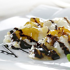 Arroz con leche con melocotón y sirope de chocolate.